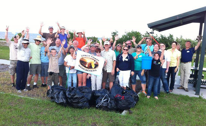 Group of Space Coast GeoCachers posing with trash cleaned up on beach