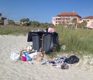 Trash spilling out from garbage cans on the beach.